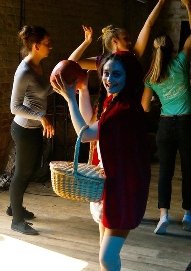Little Red Riding Hood holds a giant apple during rehearsals